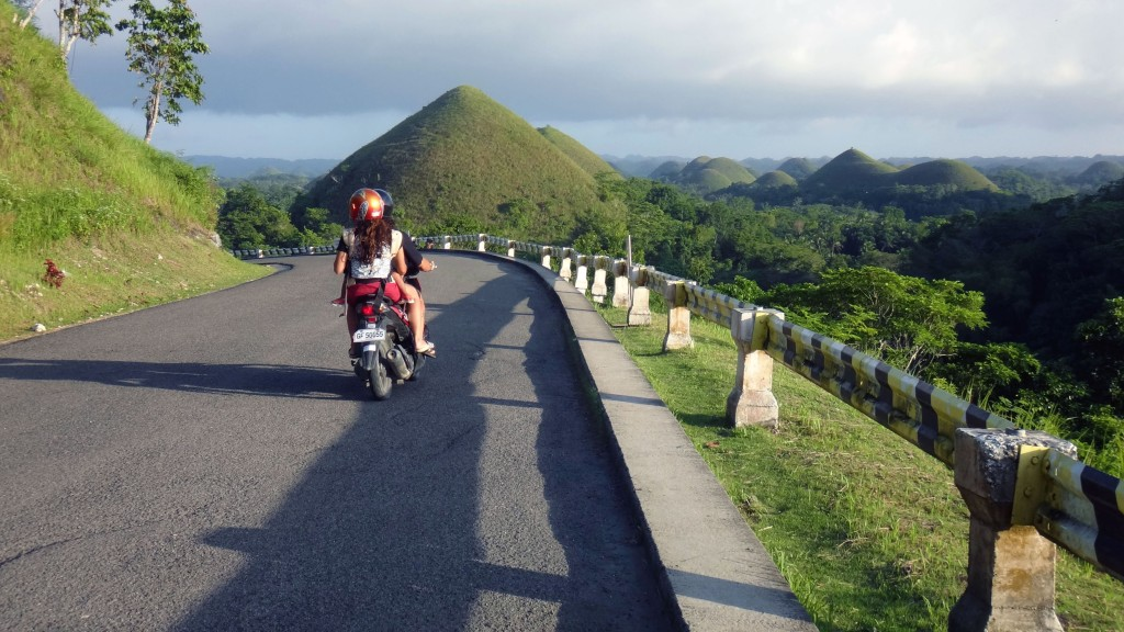 A scooter driving towards Chocolate Hills, Bohol