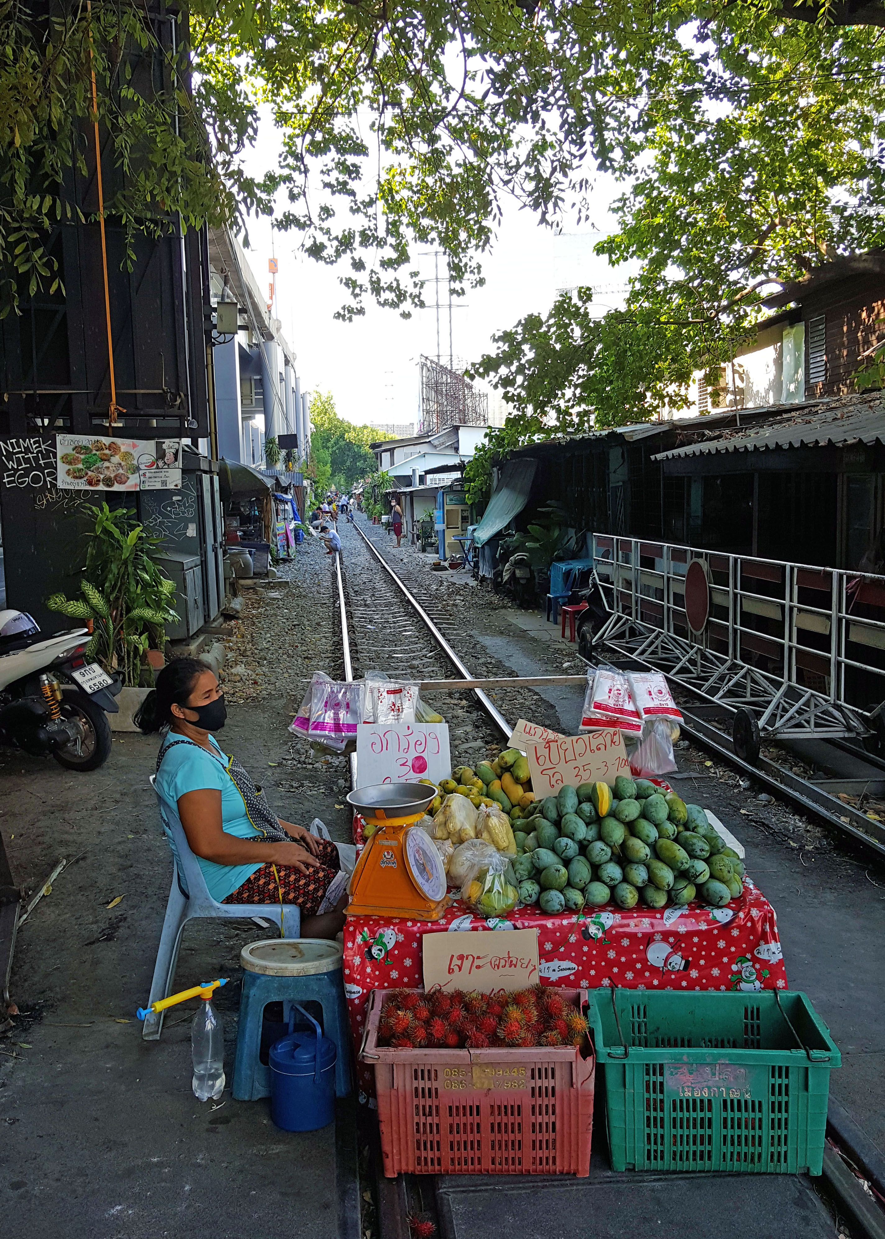 Woman selling fruits on closed traintrack
