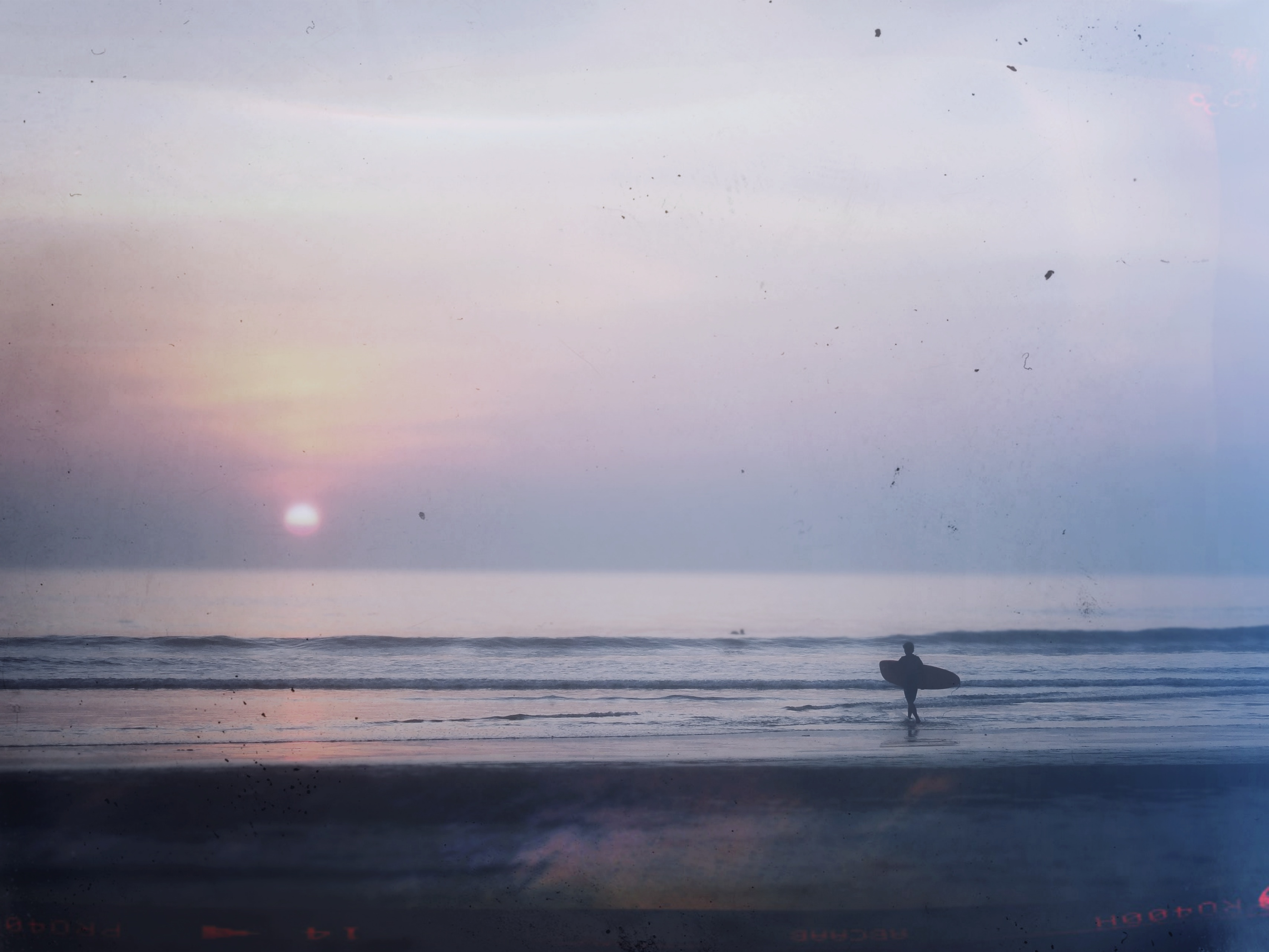 A surfer during sunset at Long Beach, Koh Phayam